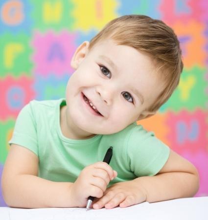 16336148 - cute little girl is writing using a pen in preschool